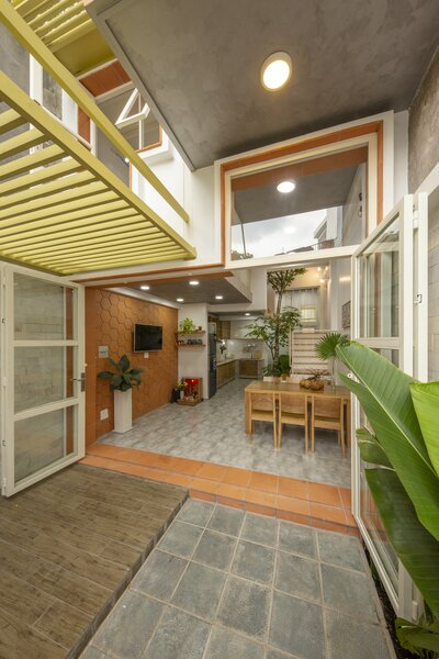 Large glass doors fold open, joining the living room and kitchen with the front courtyard.