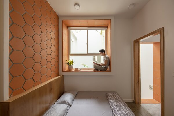 A reading nook is built into a window frame in the primary bedroom, where hexagonal terracotta tile lends color and texture.