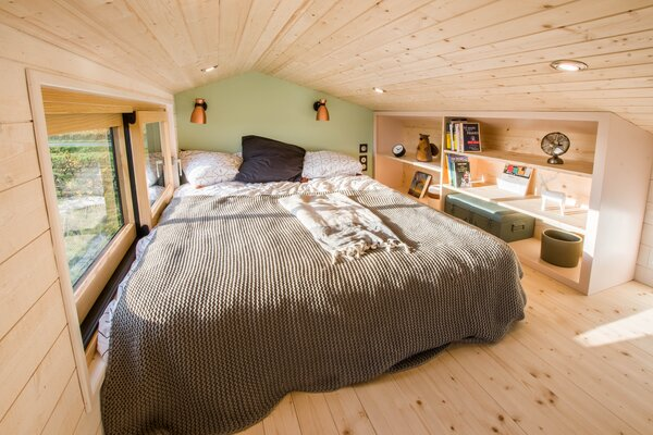 The bedroom accommodates a queen-size bed and built-in wood shelving.