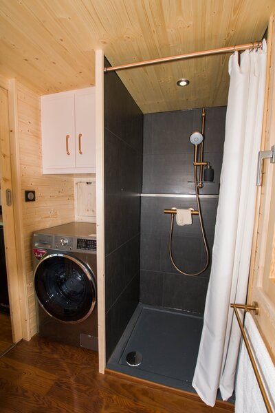 The bathroom is accessed via a partition door with a full-length mirror. The room also features a sizable shower, a dry toilet with a stainless-steel bucket and chip compartment, a large wardrobe, and a washing machine.