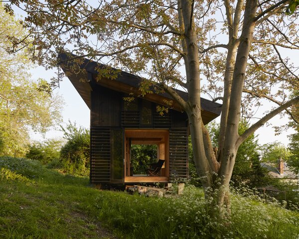 The blackened timber–clad cabin that arba designed in Longueil, Normandy, France, is marked by large glass doors, layered with wood slats that slide open and connect the home to its lush landscape.