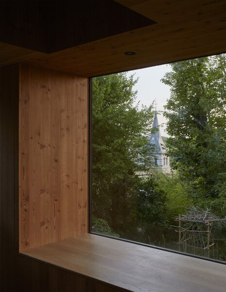 A deep window frame in the living space doubles as a sitting area and harnesses views of the garden and the village church.