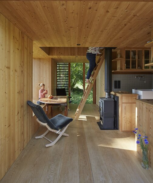 The open-plan ground floor allows the communal spaces to flow into one another. A wooden ladder accesses the lofted bedrooms.