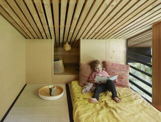The guest bedroom, which is wrapped in wood, also features a built-in storage nook.