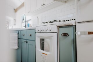 The couple outfitted the kitchen with a white retro-style range and pale-blue cabinetry.