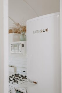The Binkerds selected marshmallow-white, retro-style appliances for the kitchen. The WINIA microwave is available from Amazon, and the Energy Star refrigerator is from Home Depot.