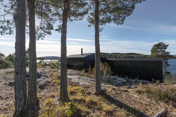 The eastern facade is tucked against the bedrock, allowing for privacy from neighboring homes.
