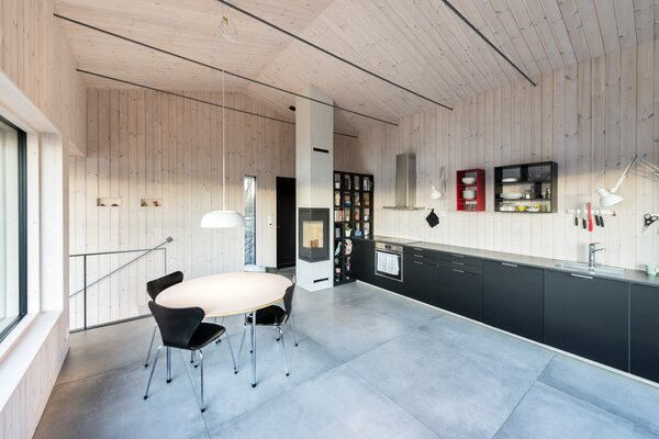 The cabin interior—including the open-plan kitchen, dining, and living areas—features a spruce-covered ceiling and walls that provide a warm aesthetic in contrast to concrete-like tile floors.
