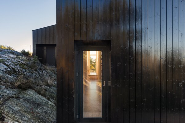 The bedrock that the cabin pushes up against creates a feeling of being nestled. A passageway with glass doors at either end floods the interior with sunlight and glimpses of the natural surround.
