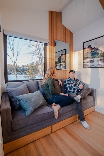 Heather and Kevin sit on a custom sofa in the living room, which features a bank of drawers underneath for storage. Above, a WarmlyYours mirror emits radiant heat and helps warm the tiny home.