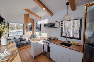 Douglas fir paneling and ceiling beams punctuate the crisp white space, complementing Baltic birch plywood cabinetry and white oak countertops in the kitchen.