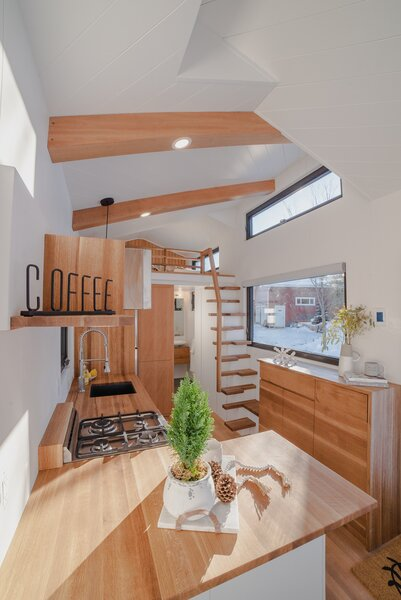 A short hall connects the kitchen to the bathroom and holds integrated shelving, a wardrobe, and an electrical box. The open stair treads leading up to the sleeping loft save on space and keep sight lines open.