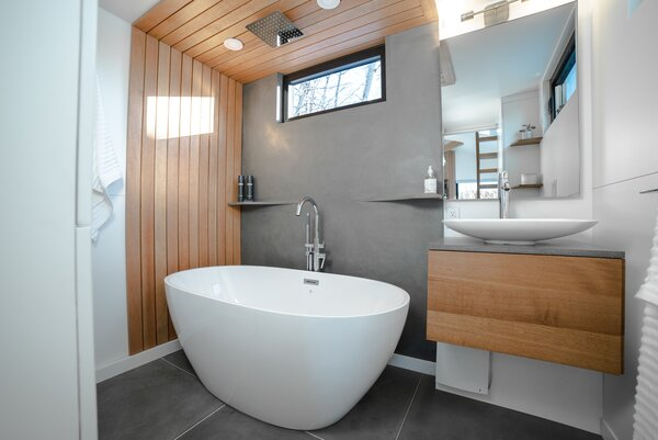 "A soaking tub with a rain shower head provides a sense of luxury in the bathroom, where a concrete wall, flooring, and vanity counter offset a white oak vanity and more Douglas fir paneling. ""Glass beads were added to the concrete before it was poured,"" Kevin tells us. ""This lightens the weight of the concrete by 37% and adds R-value."""