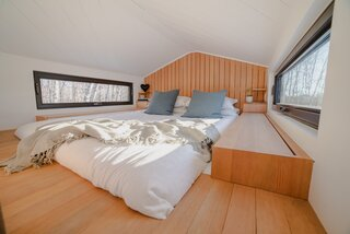 To create additional headspace in the sleeping loft, the Fritzes devised an inset in the Douglas fir flooring that accommodates a mattress. The backlit headboard and built-in storage that flank the bed are also made of Douglas fir.