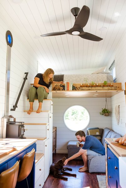 Sophia and Henry relax in the open-plan living area of their tiny home with their dog Cora, a Labrador retriever and Siberian husky mix.