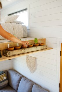 A wood ledge attached to the main sleeping loft holds planted herbs and a selection of books.