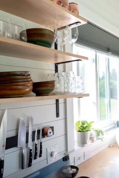 A magnetic strip that holds knives and other small cooking accessories is attached to the shiplap wall in the kitchen, helping to preserve space.
