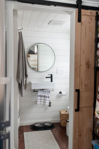 A sliding barn door accesses the bathroom, where the Jungbauers installed a compost toilet and low-flow fixtures for the sink and the shower.