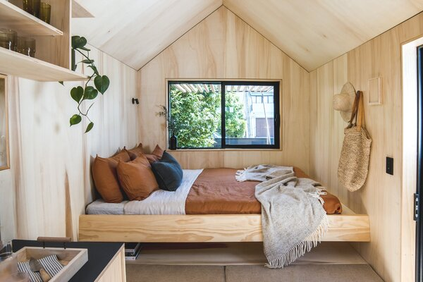 In the cabin's living area, a built-in plywood bed cantilevers above a storage area and a plywood bench padded with cushions and more storage.