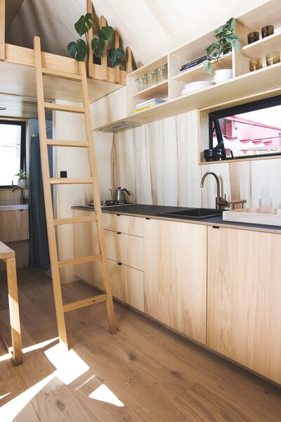 Rick outfitted the kitchen with plywood cabinetry, engineered oak flooring, and open shelving.