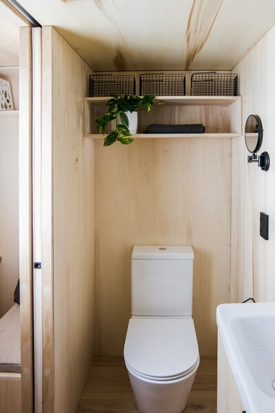 A custom plywood-and-aluminum door slides into the wall, providing access to the bathroom, which is also finished with plywood.