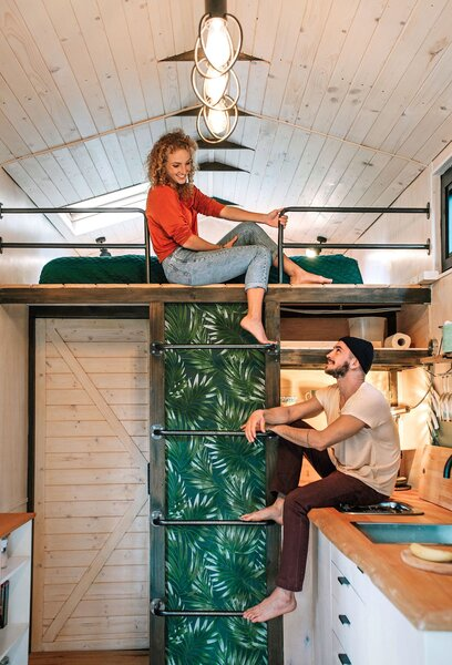 Anna and Jakob chat on the ladder that accesses the sleeping loft. Made from cast iron piping and backed with botanical wallpaper, it was designed by Anna's mother, Barbara, and built by family friend Wieslaw Siola.