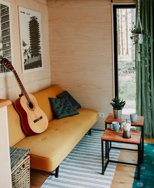 The living area is outfitted with a compact sofa, nesting coffee tables, and a green rug and drapery that reference the lush, wooded landscape.