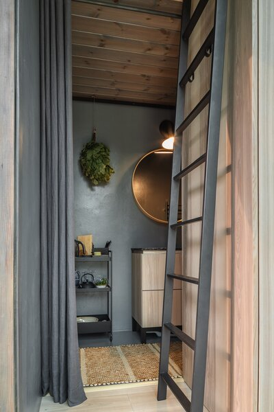 """A steel ladder leads to a sleeping loft, and a bathroom is tucked into the steel-clad portion of each cabin. """"The bathroom walls and floors are covered in a waterproof putty that has been treated with a matte varnish,"""" Tetere-Sulce says. """"This is a practical, durable solution for everyday use of the space."""""""