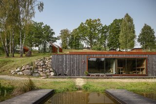 Tetere-Sulce created a glass facade for the front of the sauna building, which is built into the hillside and overlooks the ponds.