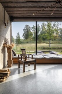 A low-slung, built-in bench runs along the expanse of glass in the sauna building, offering visitors a place to sit and ponder nature.