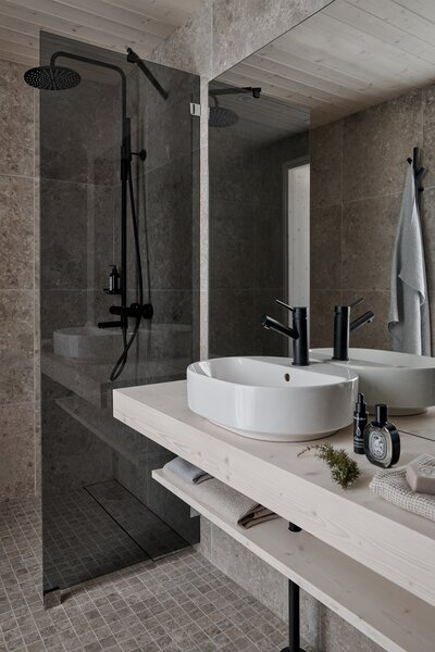 The bathrooms are outfitted with grey tile that features a stone-like appearance that references the outdoors.