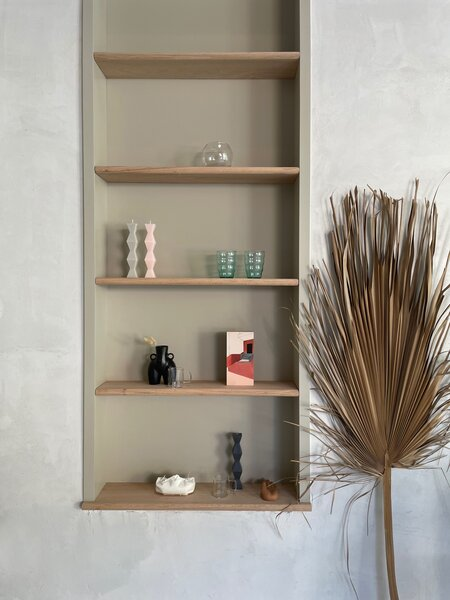 The Venezuela-born architect and designer arranged built-in shelves in the dining area with geometric candles, idiosyncratic objects, and a small painting by Colombian artist Natalie Galindo. The palm leaf beside the shelves is from a nearby park in her neighborhood.