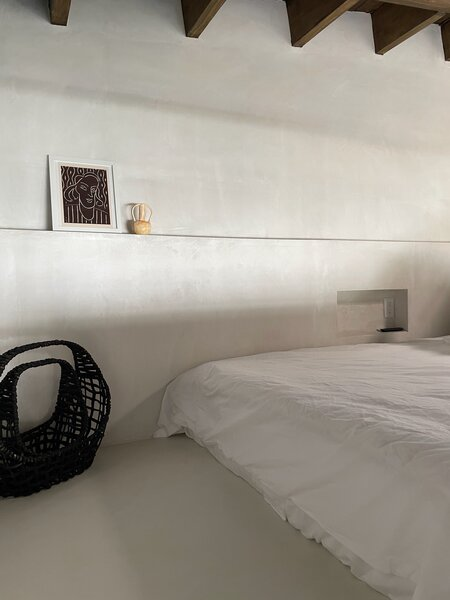 The bedroom is located in a sleeping loft above the bathroom. A built-in wall shelf and a recessed nook provide areas to place art, objects, and personal items.