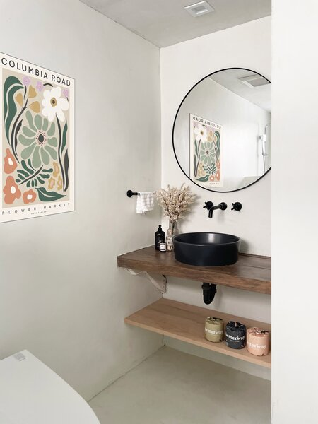 Wood shelves lend a warm note in the otherwise all-white bathroom.