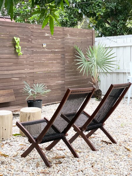 Wood-and-rope lounge chairs, a wood bench, and wood stump/tables provide an area to sit and enjoy the backyard.