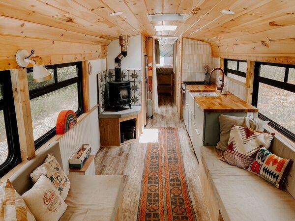 O casal equipou o ônibus com dois sofás com armazenamento embutido, uma ampla cozinha e um fogão a lenha.