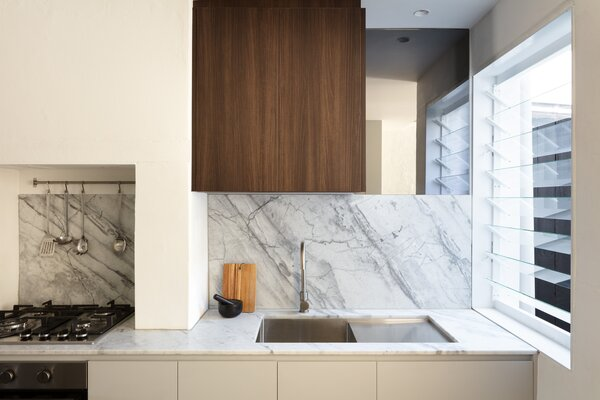 The kitchen is marked by a variety of textures that include dark walnut and marble.