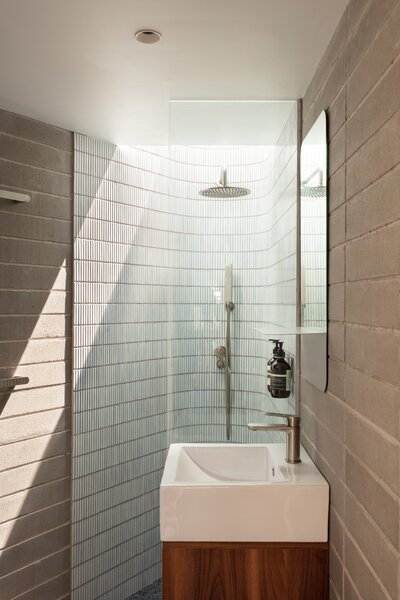 The small bathroom on the first level features concrete block walls and ceramic mosaic tile for the shower walls; a skylight in the shower supplies an indoor-outdoor experience.