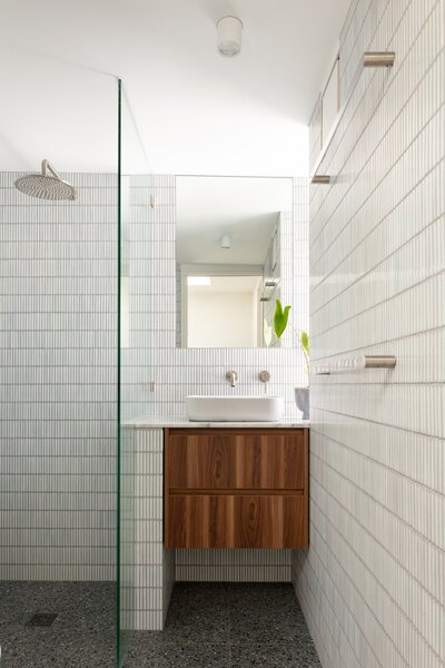 The bathroom on the second level is outfitted with terrazzo tile flooring, ceramic mosaic tile on the walls, and a walnut vanity.