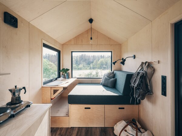 The designer clad the interior walls and ceiling with a pale birch veneer and vinyl flooring. The living area of the tiny home displays a built-in convertible table and daybed.