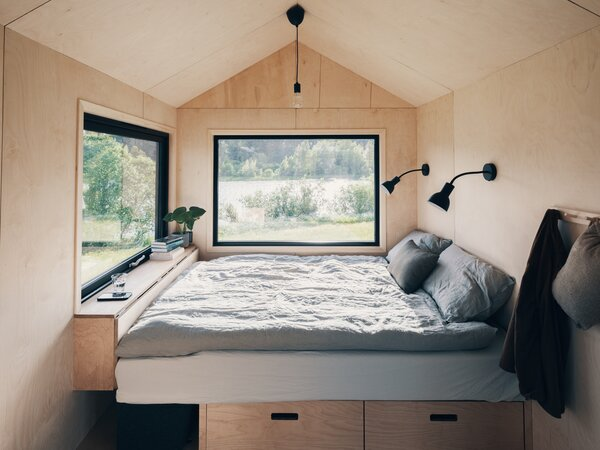 The living room daybed converts to a bed when it's time to sleep. A built-in table at the foot of the bed folds in and can be used as a nightstand or shelf.