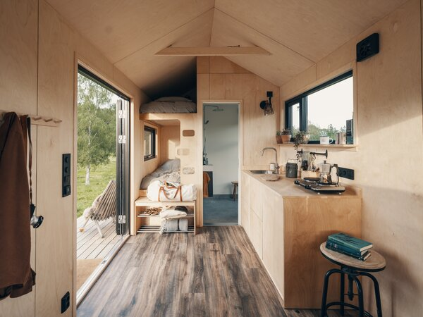 The bath and a secondary sleeping area, equipped with bunk beds, are arranged at one end of the open-plan kitchen area.