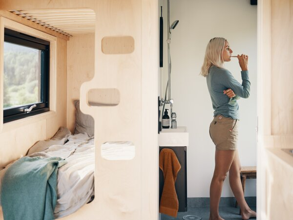 A sculptural built-in ladder accesses the bunk beds, which are adjacent to the bathroom.