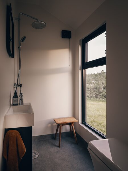The large bathroom features an open shower, a large window, and a combustion toilet.