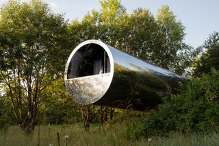 A Tubular Steel Cabin Cantilevers Above a Lush Hillside in Russia