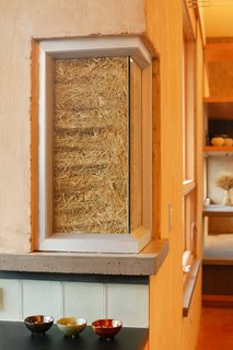 A truth window shows the straw bale insulation of the main building structure.