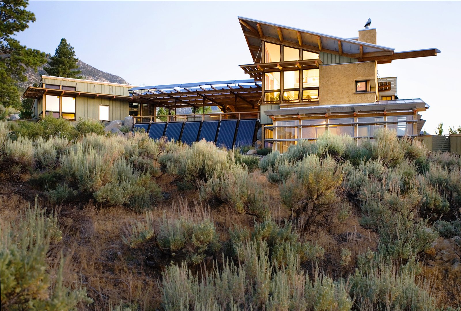 The earth finish, slatted cement board siding, and metal roofing harmonizes with the landscape and take advantage of the changing desert light.  Photo 9 of 23 in 20 Desert Homes from Eastern Sierra Residence