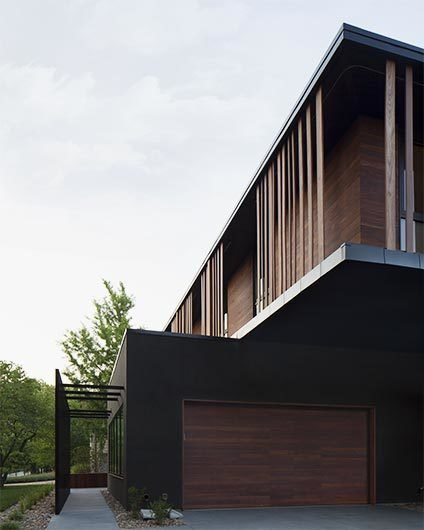 Details like vertically oriented wood siding, straight-forward forms, and overhanging masses were motivated by this modernist aesthetic. #exterior #bauhaus #wood #kansascity #baulinderhaus #hufft  Photo credit by Mike Sinclair   BauLinder Haus by Hufft