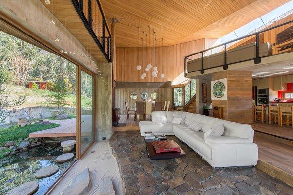 Sliding glass doors open the lower-level living room to the outdoors. Stone steps bridge the sunken biofilter pond surrounding the home.