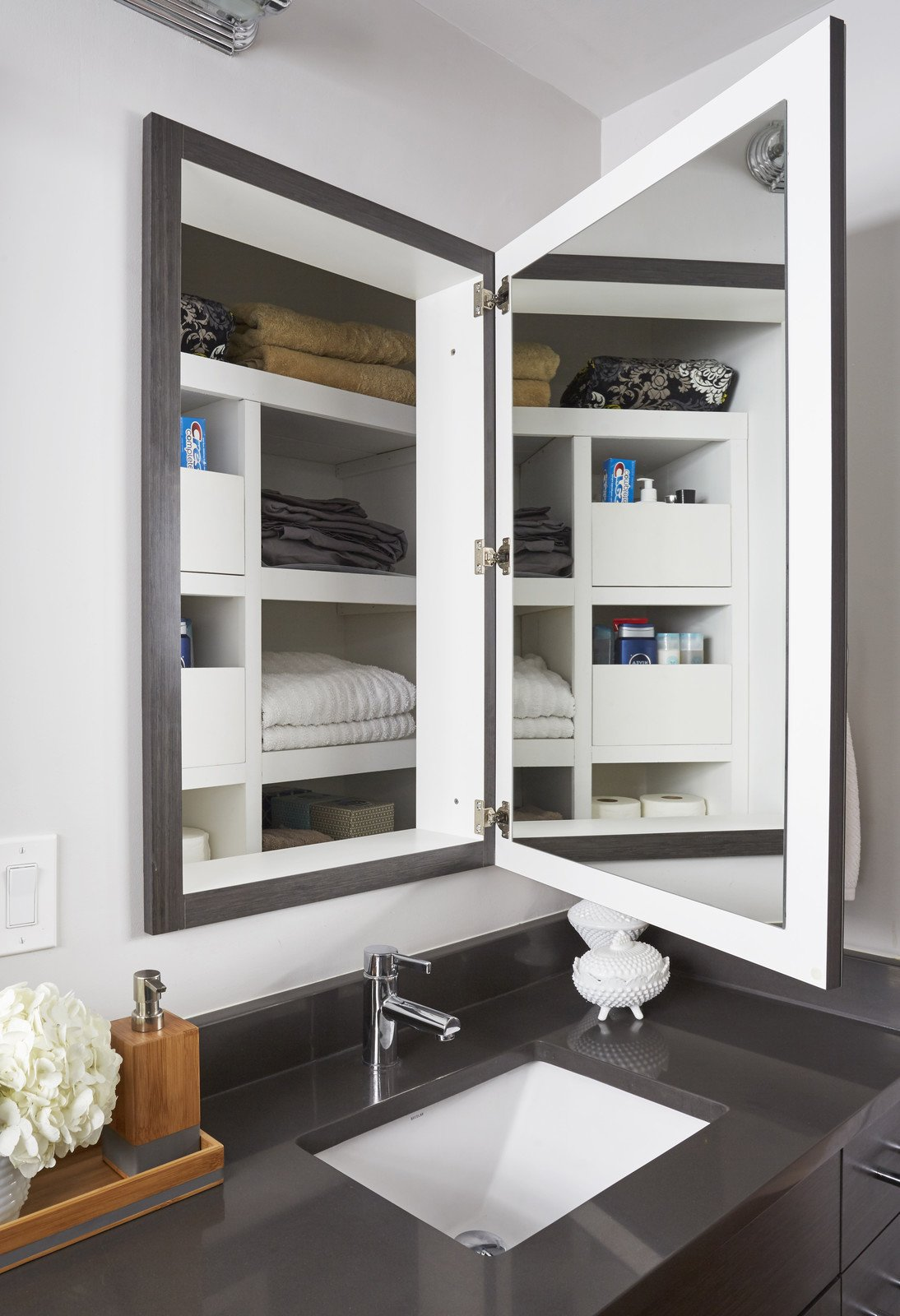 Storage Room and Cabinet Storage Type Photo caption: This renovation preserved the depth behind the medicine cabinets for linen storage.  Photo 10 of 10 in 10 Clever Ways to Sneak Storage Into Your Renovation